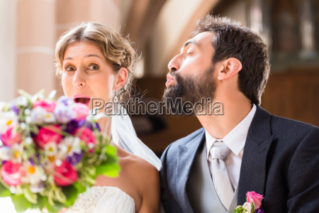 groom trying to kiss bride in