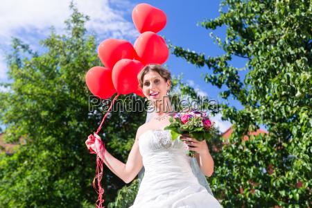 bride at wedding with read helium