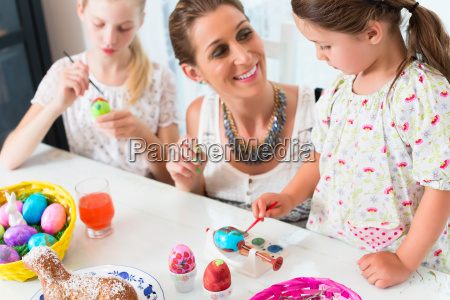 family having fun coloring easter eggs