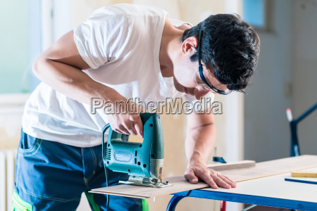 diy worker cutting wooden panel with