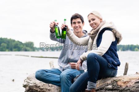 paar sitzt auf baumstumpf am flussufer