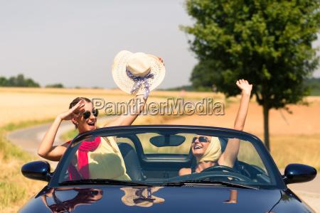 friends having summer joyride in convertible