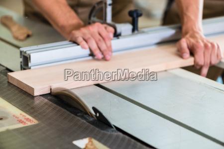 carpenter cutting wooden board with circular