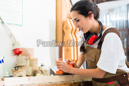 carpenter woman working with planer in