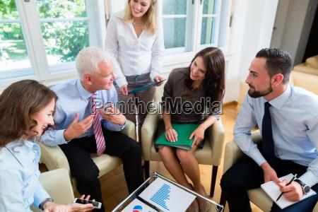five business people in team meeting