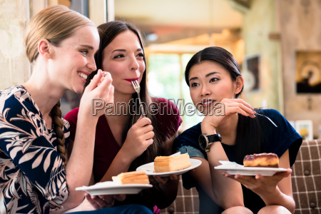 three young women eating cake indoors