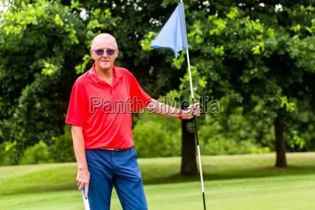 senior man playing golf on course