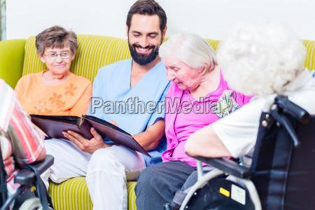 geriatrische krankenschwester blick auf bilder mit