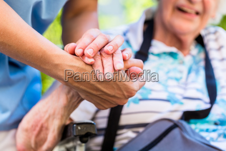 nurse consoling senior woman holding her