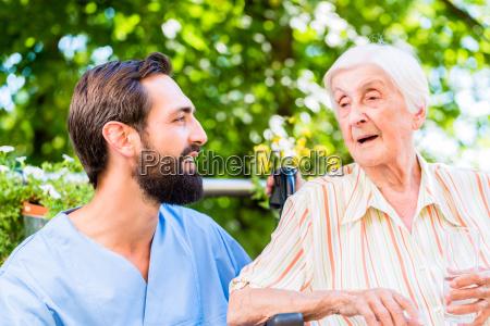 nurse having chat with senior woman