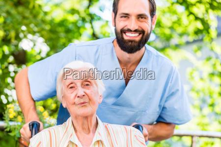 geriatrische krankenschwester drueckt aeltere dame im