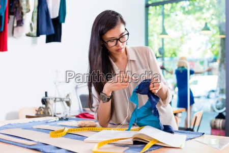 asian fashion designer woman sewing in