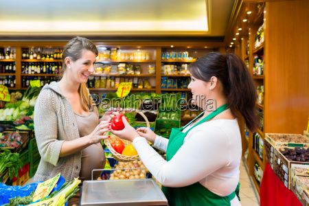 sales lady handing vegetables to woman