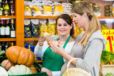 woman buying pumpkin and vegetables in