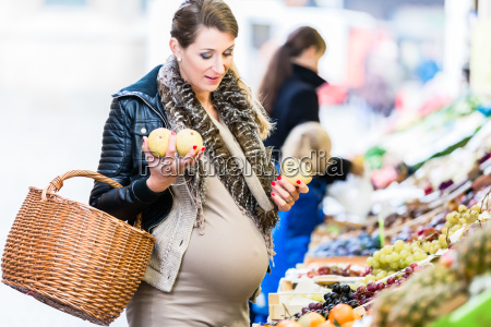 pregnant woman shopping groceries on farmers