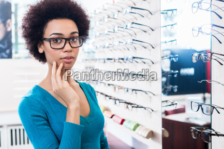 black woman trying on glasses in