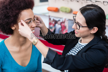 optician showing woman new glasses