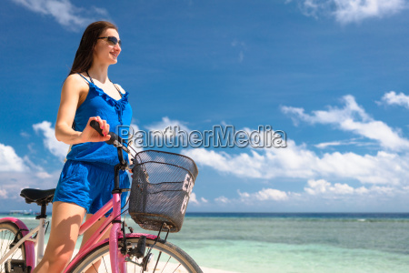 woman tourist riding bicycle at beach