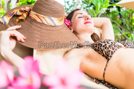woman sleeping in shade of palm