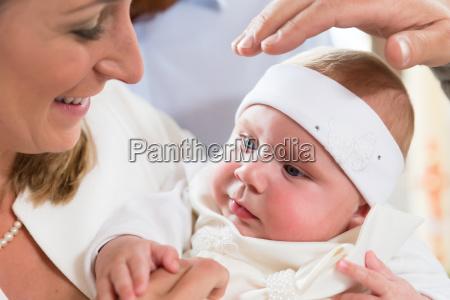mutter baby und priester hand bei