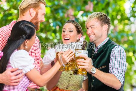 friends in beer garden clinking glasses