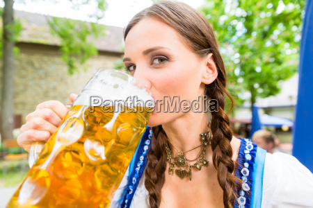 woman wearing dirndl drinking beer