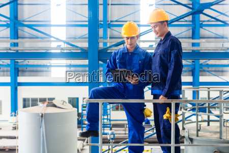 workers in large metal workshop checking