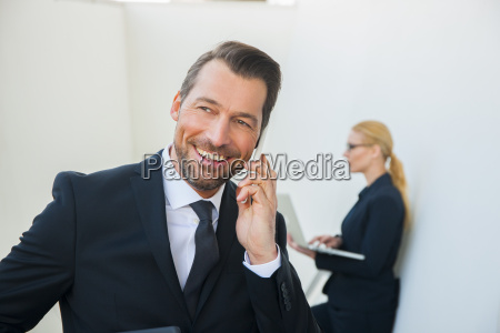 smiling businessman on cell phone and