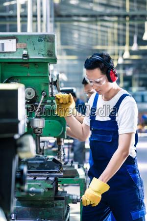 asiatische arbeiter in der produktion fabrikbohrung
