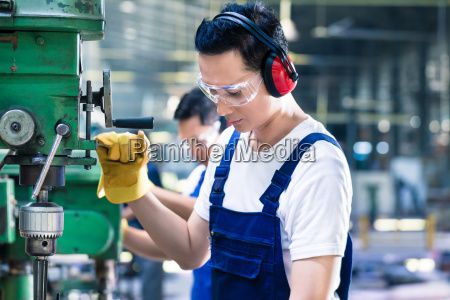 asian worker in production factory drilling