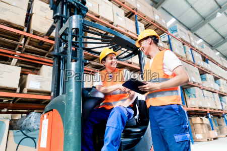 workers in logistics warehouse at forklift