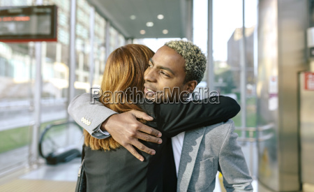 young businessman and woman embracing at