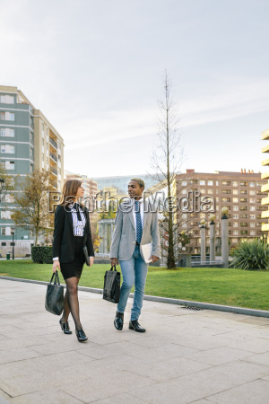 young businessman and woman walking in