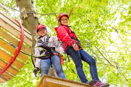 schwestern klettern im hochseilgarten zusammen