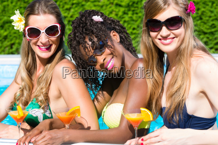 friend drinking cocktails in swimming pool