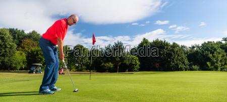 senior golf playing man putting on