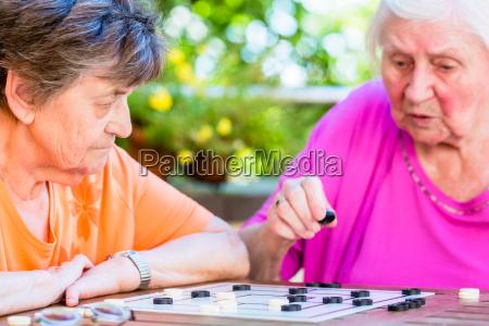 zwei aeltere damen spielen brettspiel in