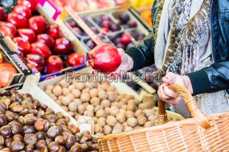woman buying fruit on market booth