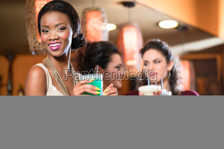group of women drinking cocktails in