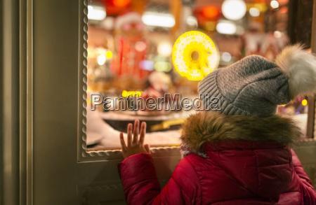 maedchen das ein weihnachtsshopfenster betrachtet