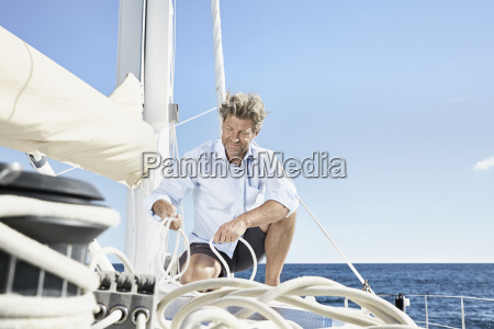 mature man working with ropes on