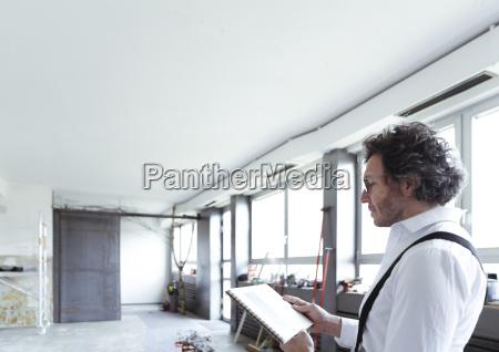 architekt mit skizzenbuch an der baustelle