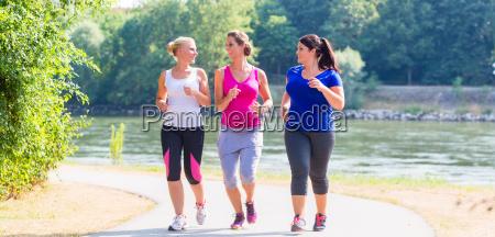 group of women running at lakeside