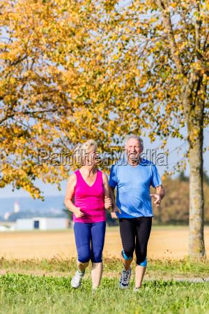 senior woman and man running doing