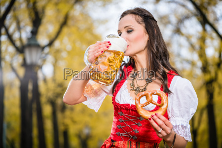 girl in traditional bavarian tracht drinking