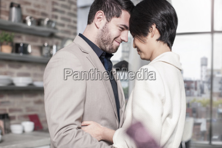 smiling couple embracing at home