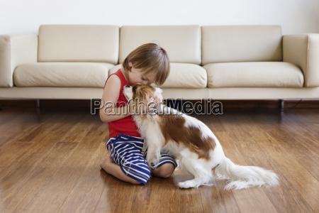 little boy cuddling his dog in