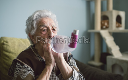 senior woman using inhaler at home