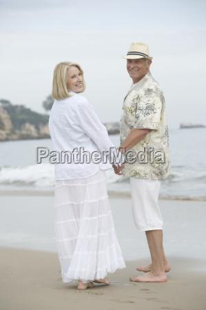 senior couple standing at beach