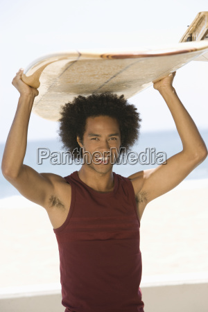 man with surfboard on head at